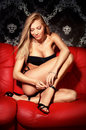Sexy young blonde lady on red leather sofa Royalty Free Stock Photo