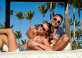 Sexy young couple relaxing near pool on a beach bed and attractive lying luxury white sun tropical garden swimming Royalty Free Stock Photos
