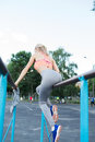 young fitness girl pulls up on street sport gym. Blonde fitness woman in sport wear with perfect fitness body on street Royalty Free Stock Photo
