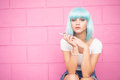 Sexy young girl in modern futuristic style with blue wig smoking cigarette over pink Royalty Free Stock Photo