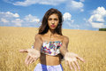 Sexy young happy girl holds hands in a wheat field Royalty Free Stock Photo