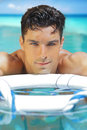 Sexy young man face and very good looking with blue eyes in tropical water Royalty Free Stock Photos