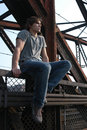 Sexy young man worker sitting on metal constructions Royalty Free Stock Image