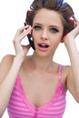 Sexy young model wearing hair rollers with phone on white background Royalty Free Stock Photos
