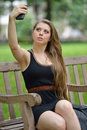 Sexy young woman in black dress taking a selfie photo brunette tank sits on park bench and snaps with her cell phone camera Stock Image