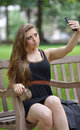 Sexy young woman in black dress taking a selfie photo brunette tank sits on park bench and snaps with her cell phone camera Royalty Free Stock Photo