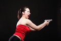 Sexy young woman gun on black background emotional girl in red with a shouting screaming Stock Images