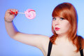 Sexy young woman holding candy redhair girl eating sweet lollipop on violet studio shot sweets Royalty Free Stock Image