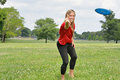 Sexy young woman jumping throwing flying disc blonde in red mesh jersey throws a in park Stock Photography