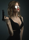 Sexy young woman in mirror sun glass holding gun studio shot Royalty Free Stock Photo
