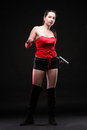Sexy young woman in red with a gun and knife on black background Royalty Free Stock Photo