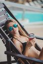 Sexy young woman relaxing on deck chair a beautiful a brunette with long straight hair sun glasses blue mirror glasses in a black Royalty Free Stock Photo