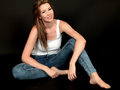 Sexy young woman sitting on floor a dslr royalty free image of attractive relaxing confidently smiling wearing blue skinny jeans Stock Photography