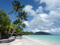 Seychelles landscape of white sandy beach turquoise water coconut trees blue and sunny sky with some white clouds Royalty Free Stock Photo