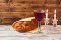 Shabbat concept with wine glass and challah bread on wooden table Royalty Free Stock Photo