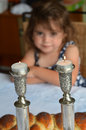 Shabbat eve jewish girl looks at lit sabbath candles before dinner Royalty Free Stock Images