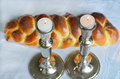 Shabbat eve lit shabbath candles with uncovered challah bread and kippah Royalty Free Stock Image