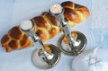 Shabbat eve table with uncovered challah bread lit sabbath candles and kippah Stock Image