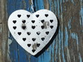 Shabby chic metal heart hanging on old blue grunge background Royalty Free Stock Photography