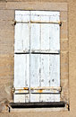Shabby white painted window shutter worn on stucco wall Stock Photography