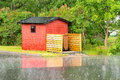 Shack in rain small red with garbage bins outside is falling and street front of hut is wet drops hit the asphalt Stock Photography