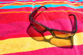 Shades on beach towel Stock Photos