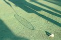 Shadow on the ground with badminton racket and old shuttlecock Royalty Free Stock Photo