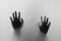 Shadow hands of the Man behind frosted glass.Blurry hand abstraction.Halloween background.Black and white picture Royalty Free Stock Photo