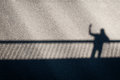Shadow of a man waving from a bridge Royalty Free Stock Photo