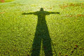 Shadow of the person in the form of a cross on a grass Royalty Free Stock Photo