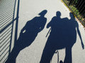 Shadows on the bridge of a man with two woman one either side with a safety railing right Royalty Free Stock Photos