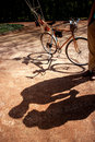 Shadows of couple standing in the park alley with bicycle and a airship on it on background Stock Photo