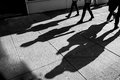 Shadows of four walking pedestrians shadow projected on the sidewalk Royalty Free Stock Photography