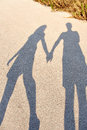 Shadows of lovers the a boy and girl holding hands on a sunny day Stock Photography