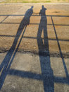 Shadows of two people elongated on a dirt floor on a warm summer evening Royalty Free Stock Photos