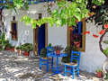 Shady place in greece two chairs and a table typical painted blue front of a house Stock Image