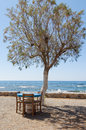 Shady place under a salt cedar at the beach table and chairs mediterranean sea in village frangokastello Royalty Free Stock Photography