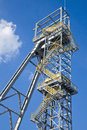 Shaft mine tower of a coal with white cloud and blue sky Royalty Free Stock Image