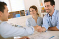 Shake hands for concluding project young couple meeting construction planner Stock Photo