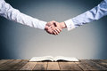 Shake hands on open books Royalty Free Stock Photo