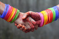Shaking hands decorated with colorful bracelets Royalty Free Stock Photography