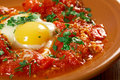 Shakshuka dish of eggs poached in a sauce of tomatoes chili peppers and onions often spiced with cumin moroccan tunisian libyan Royalty Free Stock Image