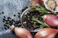 Shallots peppercorns garlic and rosemary black bulb over dark slate top view Stock Images