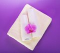 Shampoo and balm conditioner on terry towel a with an orchid flower the violet Royalty Free Stock Image
