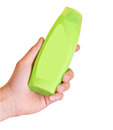 Shampoo container in hand isolated with green plastic on white background Royalty Free Stock Photo