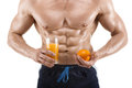 Shaped and healthy body man holding a glass with juice and orange, shaped abdominal, isolated on white Royalty Free Stock Photo