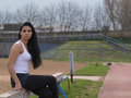 Shapely girl looking at you long black haired and sitting on the sports equipment Royalty Free Stock Photo