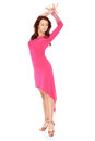 Shapely woman posing in a sexy pink dress beautiful with cut away front high heels with her arms raised isolated on white Royalty Free Stock Photo