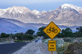 Share the road with bicycles sign along a rural leading across owens valley towards distant mountains Stock Images