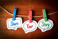 Share your story paper speech bubbles with text hanging on the line against dark wooden background Stock Photography
